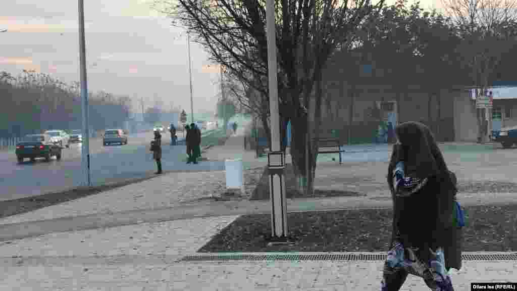 Түтін иісі мен күннің суығынан бетін жауып бара жатқан тұрғын. Түркістан қаласы, 22 қараша 2019 жыл.