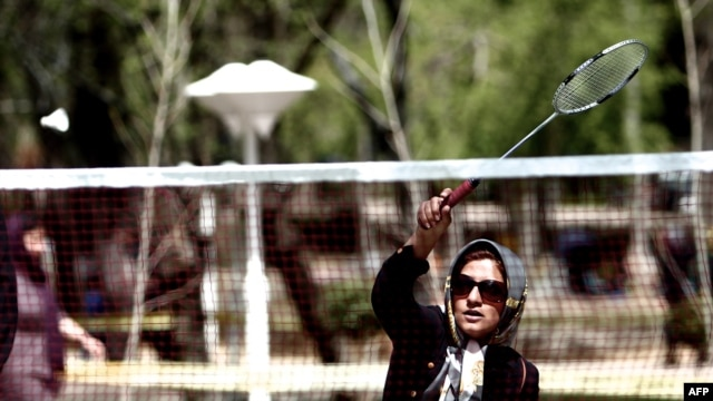 A woman plays badminton in a Tehran park.