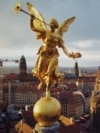 The golden sculpture of Pheme, the personification of fame and renown in Greek mythology, on the roof of the Dresden University of Visual Arts in Dresden, Germany, with the rebuilt Frauenkirche, which was destroyed in World War II bombing, in the background. (RFE/RL/Amos Chapple)