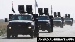 Iraqi forces drive towards Kurdish Peshmerga positions on October 14 on the southern outskirts of Kirkuk.