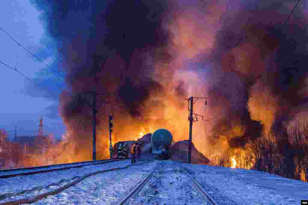 Russian firefighters try to extinguish burning compressed-gas tanks that ignited after a train derailed in the city of Kirov on February 5. (epa)
