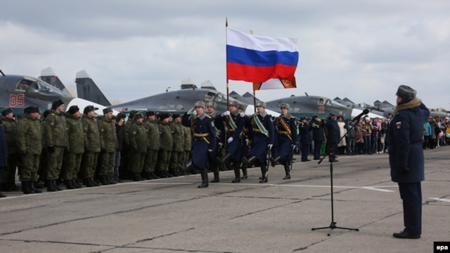 "Participants attend a ceremony to welcome Russian military jets and pilots upon their return to a domestic airbase on March 15, not long after President Vladimir Putin announced that they had ""generally accomplished"" their objectives in Syria."