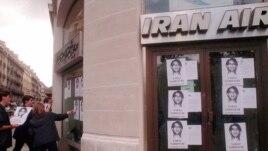 اعضای سازمان گزارشگران بدون مرز در اعتراض به بازداشت فرج سرکوهی عکس های وی را بر روی شیشه دفتر «ایران ایر» در پاریس می چسبانند.