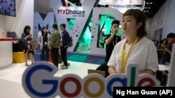 Visitors talk to staff members at a Google stand during the Global Mobile Internet Conference (GMIC) in Beijing, China, Friday, April 28, 2017.
