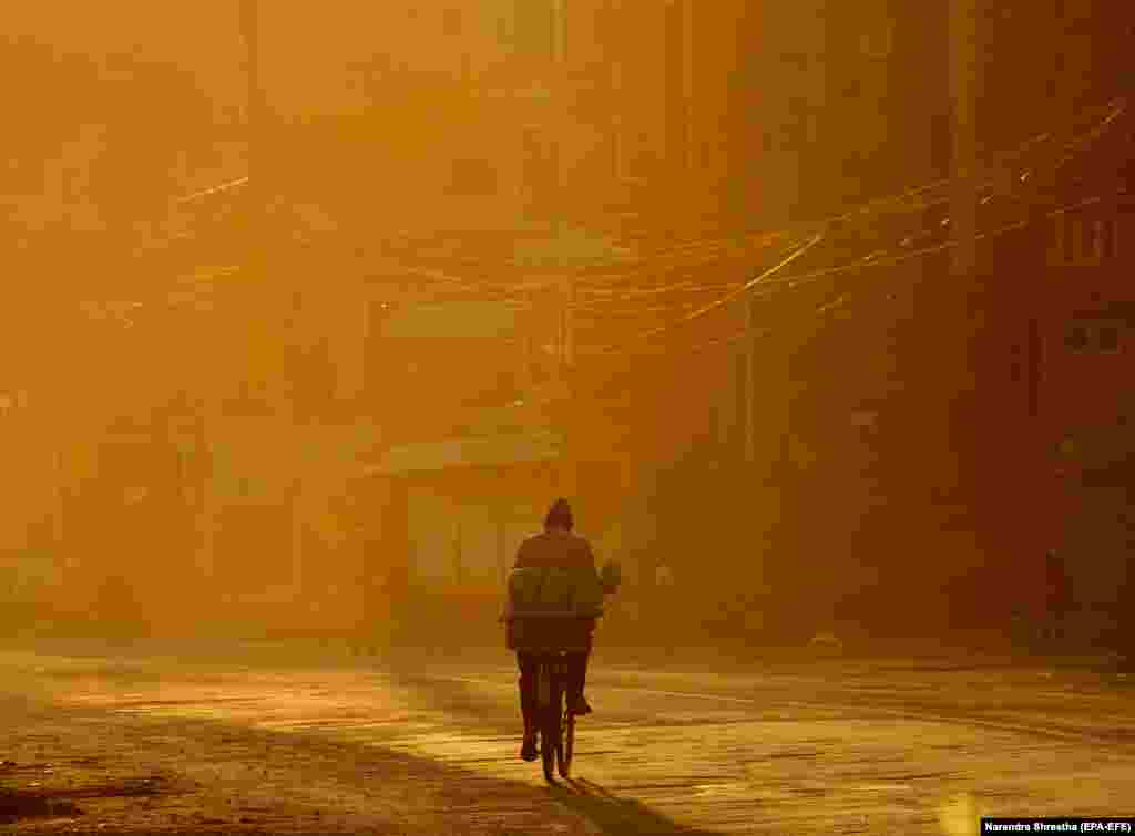 A man rides his bicycle in the early morning hours during the coronvirus lockdown in Kathmandu, Nepal. (epa-EFE/Narendra Shrestha)