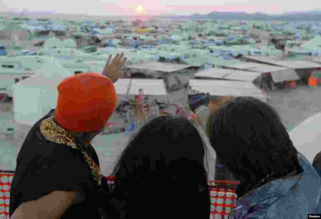 Participants gesture toward the rising sun at the 2013 Burning Man arts and music festival in Nevada's Black Rock desert.
