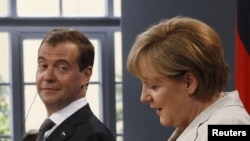 Russian President Dmitry Medvedev (left) looks toward German Chancellor Angela Merkel at a news conference in Hanover on July 19.