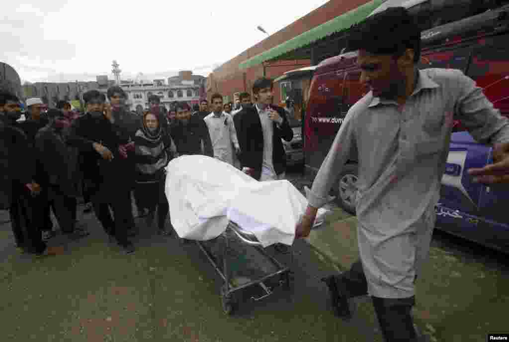 A man wheels the body of a woman killed in the earthquake at the Lady Reading Hospital in Peshawar, Pakistan.
