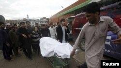 Мужчина несет на носилках тело женщины, которая умерла в результате землетрясения в больнице Леди Рединг. Пешавар, 26 октября 2015 года.