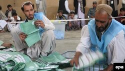 Afghan workers of the Afghan Independent Election Commission (IEC) count presidential ballots on April 5 at a polling station in Kandahar.