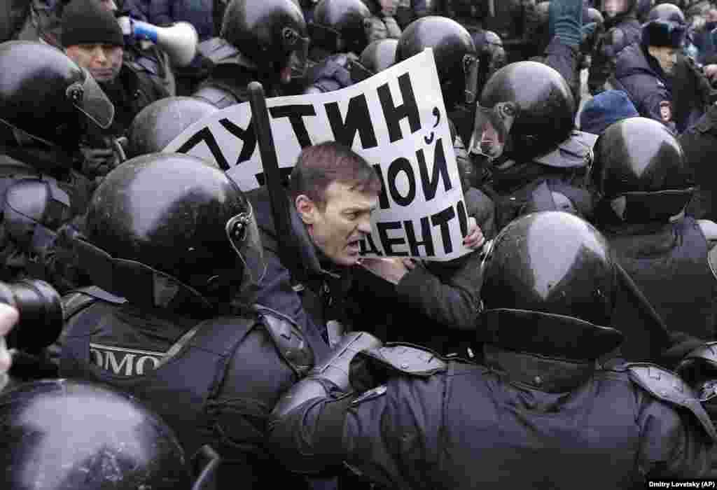 Ресейдегі президент сайлауына байкот жариялауға шақырған шеруде полиция наразылардың бірін ұстап жатқан сәт.
