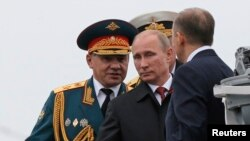 Russian President Vladimir Putin (center) and Defense Minister Sergei Shoigu (left) review the Russian fleet in Sevastopol on May 9.
