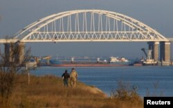 A Russian cargo ship is seen beneath the Kerch Bridge connecting the Russian mainland with the Crimean Peninsula on November 25.
