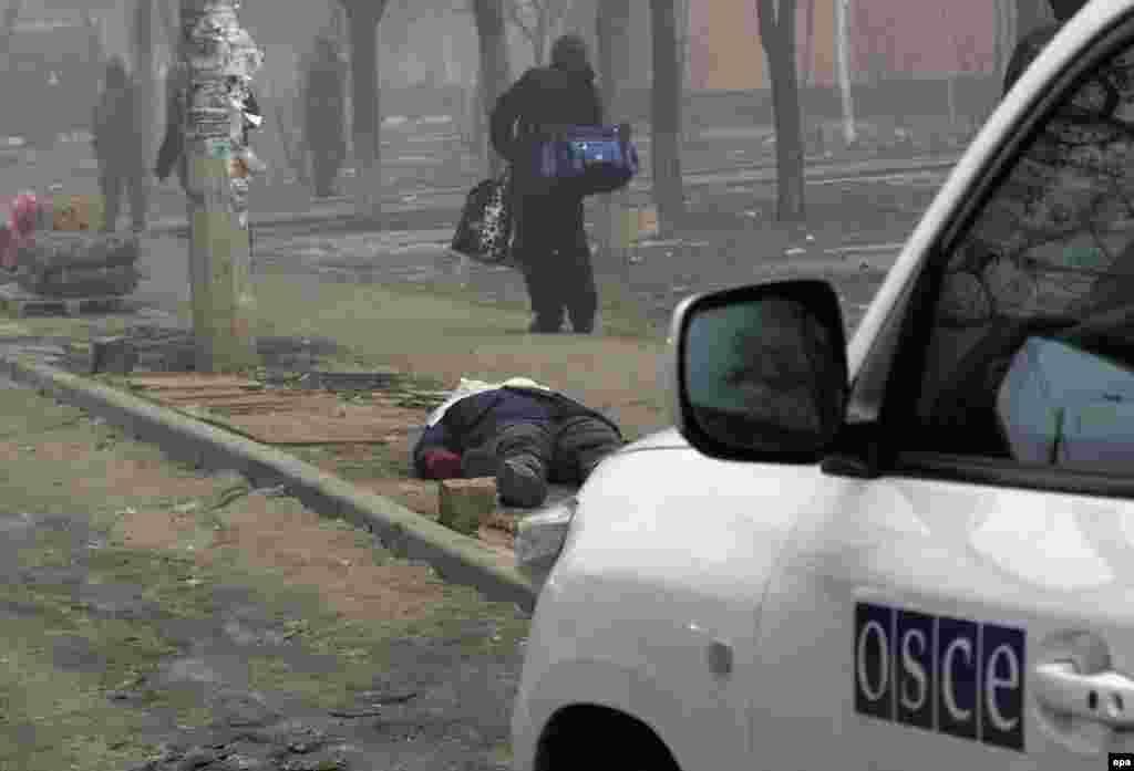 Мариупольді әскери қарудан атқылау салдарынан мерт болған адамның мүрдесі жатқан маңда тұрған Еуропадағы қауіпсіздік және ынтымақтастық ұйымының көлігі. 24 қаңтар 2015 жыл.