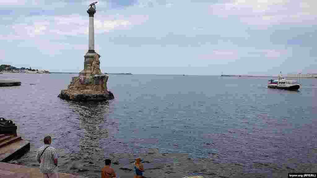 На пляжі в центрі Севастополя біля пам'ятника Затопленим кораблям тепер мало хто купається, бо місцева влада погрожує великими штрафами за купання у невстановленому місці