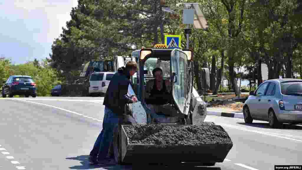 Строители возят бетон в ковше мини-бульдозера прямо по трассе, проходящей через Сапун-гору