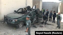 FILE; Afghan policemen inspect a damaged police vehicle after a suicide attack in Kabul.