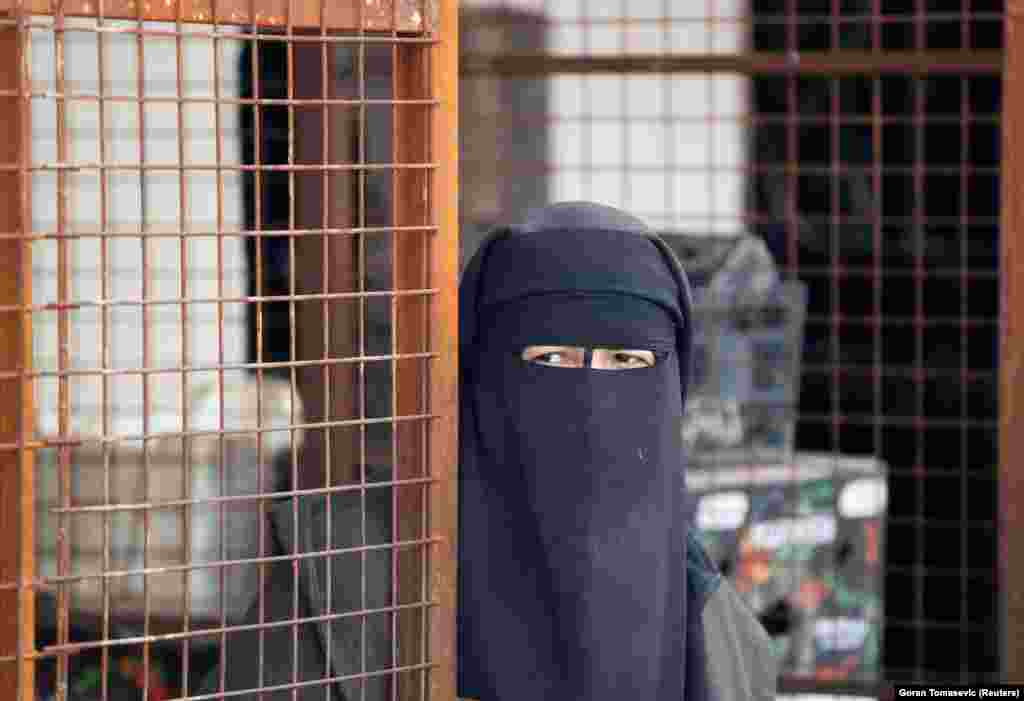 A woman looks out at the al-Hol camp.
