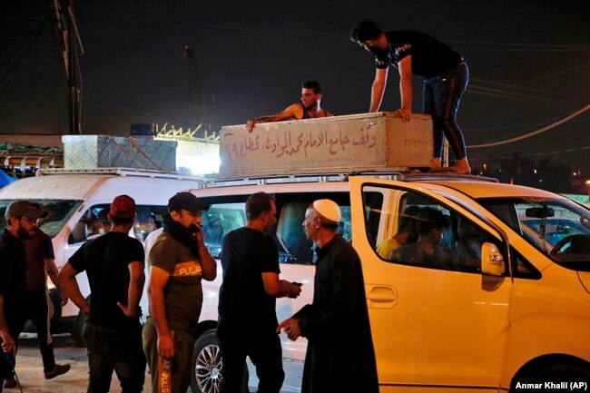 Mourners load the coffin of Saleh Ahmed, 27, a protester killed in an anti-government demonstration, during his funeral in Najaf, Iraq, Monday, Oct. 28, 2019.