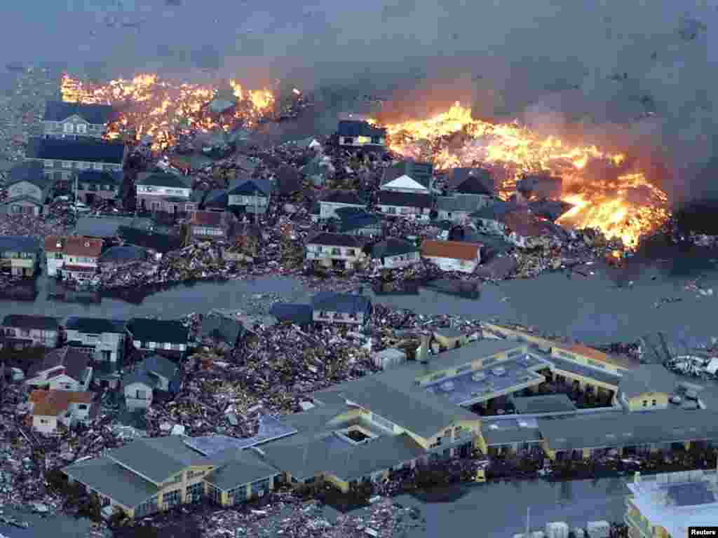 Burning houses are swept out to sea in Natori, northeastern Japan, after the strongest earthquake on record and a massive tsunami struck the coast on March 11. (Reuters/Yomiuri)