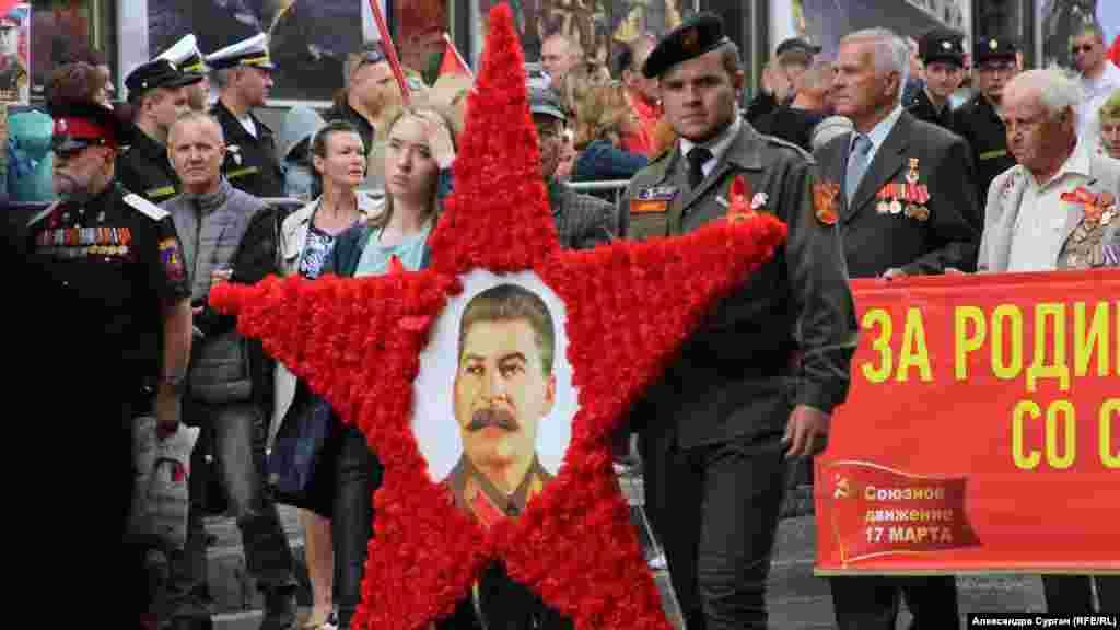 Parad iştirakçileri İosif Stalinniñ suretini tutıp yürüş yapalar