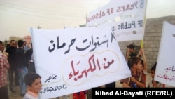 أطفال يحملون لافتات عن نقص الكهرباء في كركوك