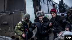 An elderly Ukrainian man is helped by a Ukrainian Army soldier and a citizen during the evacuation of civilians in Debaltseve, in the Donetsk region, on February 3.