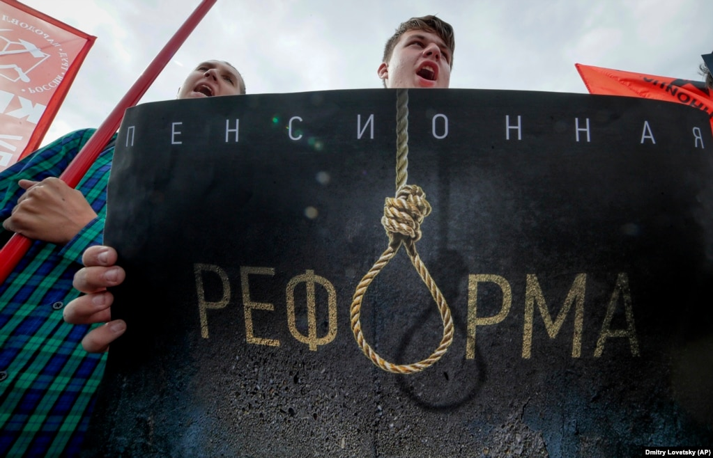 "People shout slogans as they hold a poster reading ""Pension Reform"" during a Communist Party rally protesting hikes in the retirement age in St. Petersburg. Several thousand people gathered in central Moscow and St. Petersburg on September 2. Other demonstrations were reported in Vladivostok in the Far East and Barnaul and Novosibirsk in Siberia. (AP/Dmitri Lovetsky)"