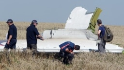 Investigators examine a piece of debris from Malaysia Airlines flight MH17, which was shot down over separatist-held territory in eastern Ukraine in July 2014.