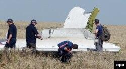 Australian and Dutch investigators examine a piece of debris of Malaysia Airlines Flight MH17 near the Ukrainian village of Hrabove.