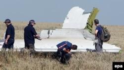 """ავსტრალიელი და ჰოლანდიელი ექსპერტები ათვალიერებენ """"მალაიზიის ავიახაზების"""" თვითმფრინავის ფრაგმენტს. 2014 წელი, დონეცკის ოლქი"""