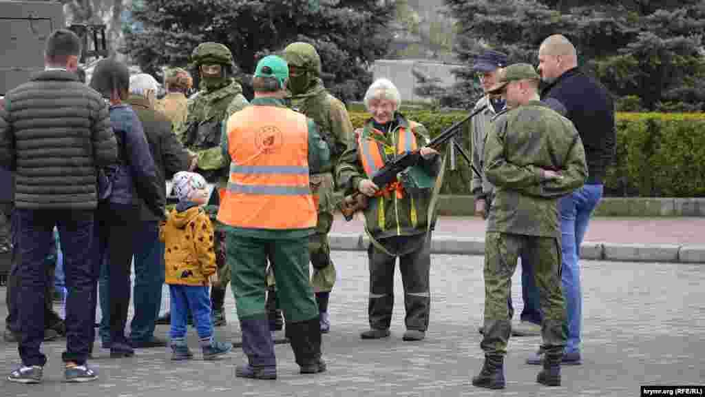 Пенсионерка с ручным пулеметом, рядом с ней российский военный
