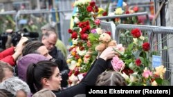 People gather at the crime scene near Ahlens department store in central Stockholm on April 8.