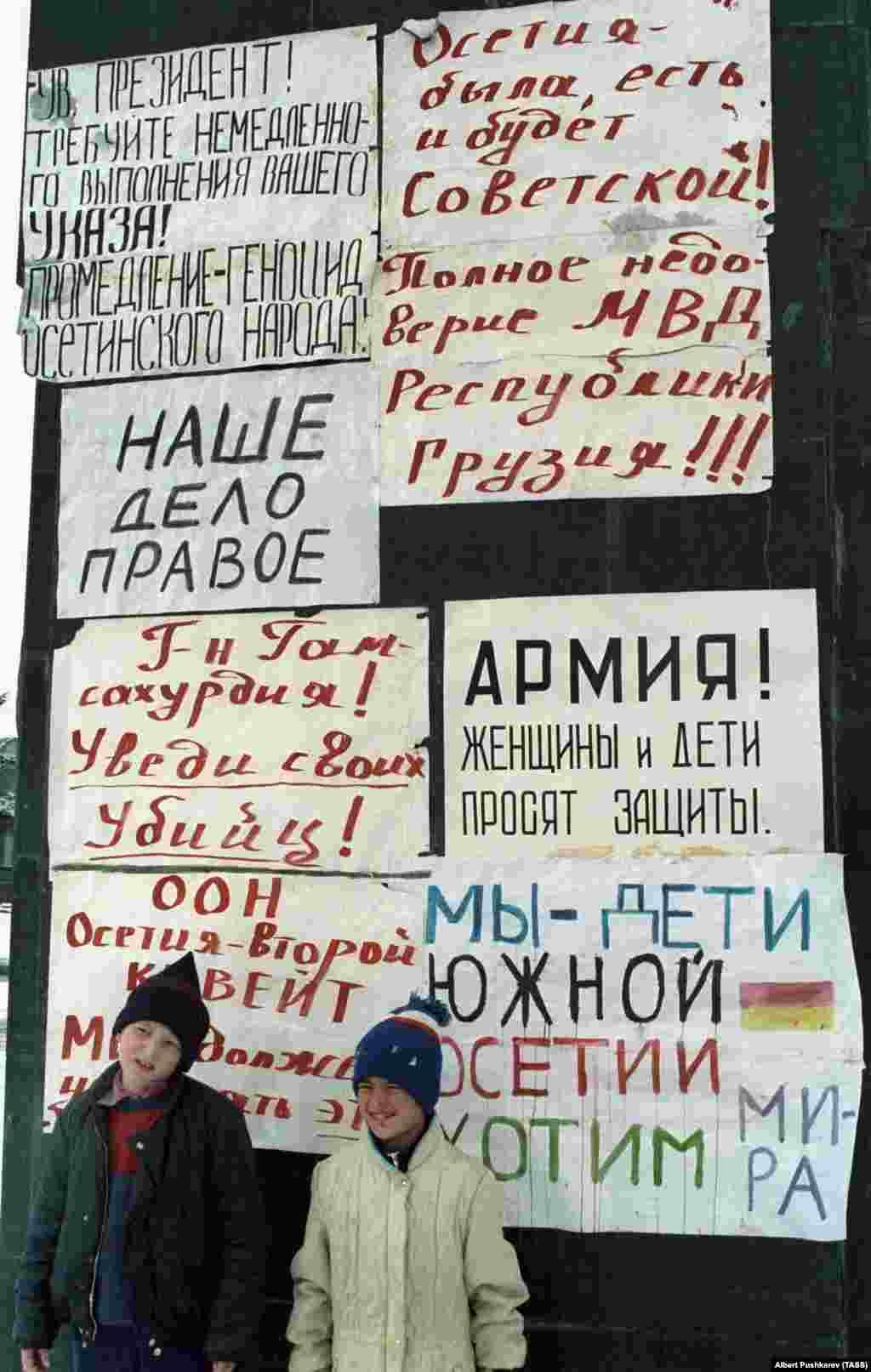 """GyerekekChinvaliutcáin 1991. január 1-jén. A hátuk mögött olvasható feliratokon ez áll: """"Oszétia mindig is szovjet volt és az is marad!"""". A grúzok közül sokan árulóknak tartották Oszétia lakóit, miközben az ország a Szovjetunióból való kiválásért harcolt. Mindeközben az oszét nép kirekesztve érezte magát azok miatt az új törvények miatt, amelyek a grúzt ismerték el egyetlen hivatalos nyelvként, és meggyengítették az oszét politikai képviseletetTbilisziben."""