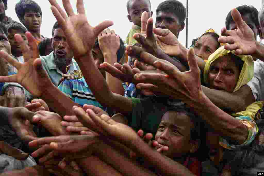 Refugees reach for food aid at the Kutupalong refugee camp in Ukhiya, near the Bangladesh-Burma border.
