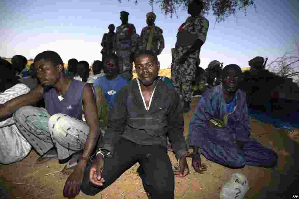 Malian soldiers guard handcuffed prisoners after they arrived by boat in Kadji on the Niger River on March 1. (AFP)