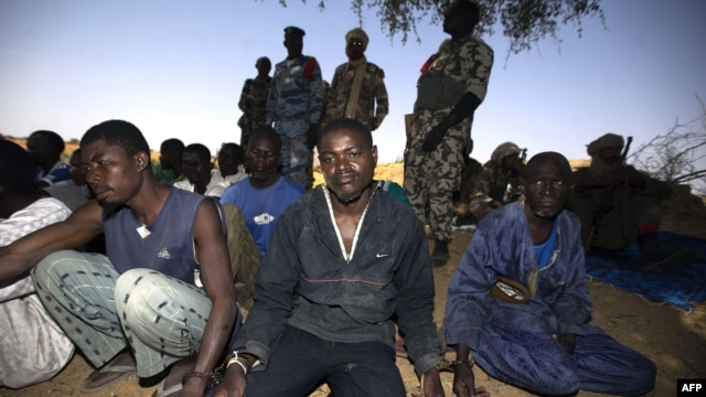 Soldiers guard handcuffed prisoners on March 1 after French and Malian troops reportedly launched an operation the previous day in the village of Kadji, northern Mali, where Islamists are hiding out on an island on the Niger River.