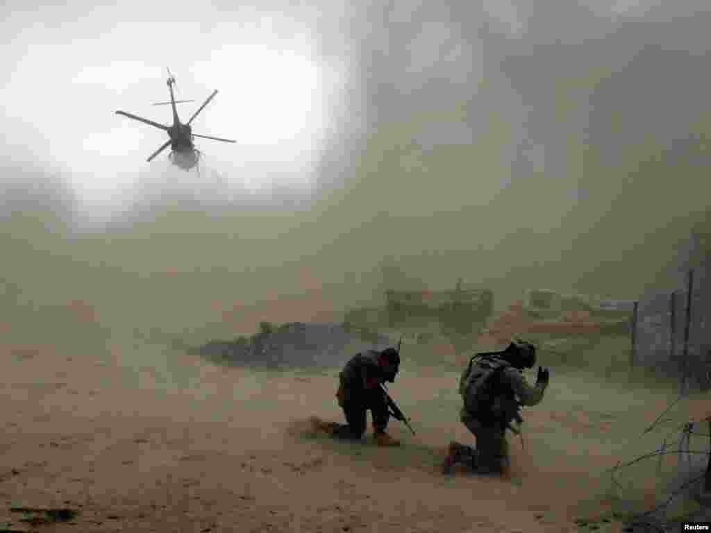Американські солдати з 101-ї повітряно-десантної дивізії проводжають вертоліт медичної евакуації на півночі долини Аргандаб у провінції Кандагар, 30 липня. Один із солдатів втратив ногу, а інший був поранений осколком внаслідок вибуху саморобного вибухового пристрою під час патрулювання.Photo by Bob Strong for Reuters