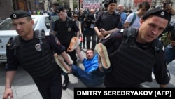 Российские полицейские уносят ЛГБТ-активиста Николая Алексеева, участвовавшего в несанкционированной акции протеста в поддержку прав секс-меньшинств. Москва, 30 мая 2015 года.