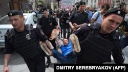 Сексуалдык азчылыктарды колдоп, маршка чыккан ЛГБТ-активисти Николай Алексеевди полиция кызматкерлери көтөрүп баратышат.
