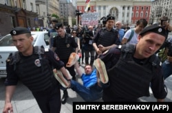 Russian riot police detain LGBT activist Nikolai Alekseyev during an unauthorized rally in central Moscow in May.