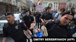 Russian riot police detain gay rights activist Nikolai Alekseyev during an unauthorized gay-rights rally in central Moscow in May.