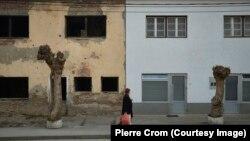 Сребреница, Босния и Герцеговина - Жительница Сребреницы проходит мимо здания, разрушенного во время войны 1992-1995 годов в Боснии. В Сребренице избран новый мэр, который отрицает факт геноцида боснийских мусульман. Младен Груичич - первый сербский мэр Сребреницы