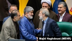 Iranian Parliament speaker Ali Larijani (2nd R) shaking hand with his second deputy Ali Motahari, After both re-elected in parliament session on Wednesday May 31, 2017.