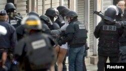 Полиция арнайы жасағы Сен-Дени ауданында шабуылға қатысы бар деген күдіктілердің бірін ұстап әкетіп барады. Париж, 18 қараша 2015 жыл.