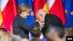 Владислав Бартошевский - советник премьер-министра Польши по вопросам международного диалога приветствует канцлера Ангелу Меркель на открытии выставки в честь польско-немецкого примирения