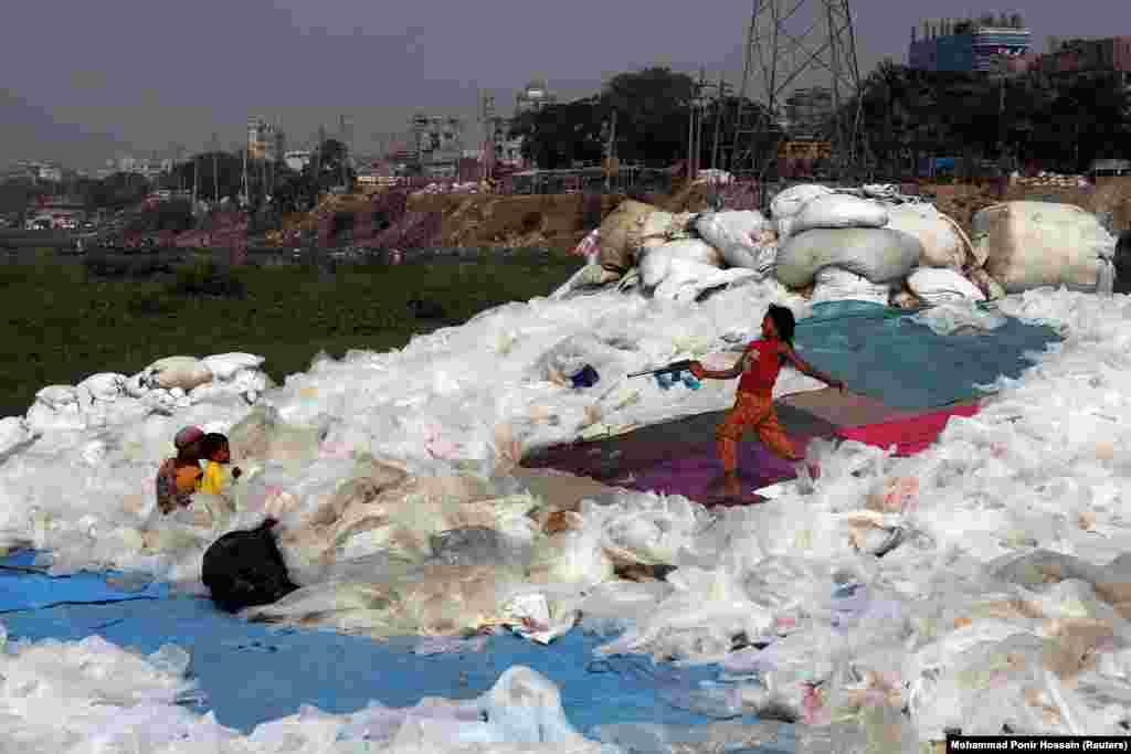 A girl plays with a toy gun at a plastics recycling yard in Dhaka, Bangladesh. (Reuters/Mohammad Ponir Hossain)