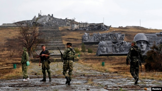 Pro-Russian separatists walk toward a destroyed war memorial at Saur-Mohyla, a hill east of the city of Donetsk, on August 28.
