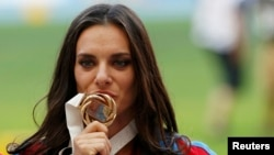Russia's Yelena Isinbayeva kisses her gold medal at the women's pole-vault victory ceremony during the IAAF World Athletics Championships in Moscow on August 15.