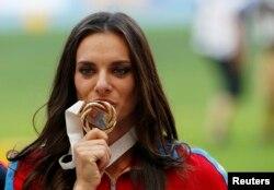 Ресейлік спортшы Елена Исинбаева алтын медалін сүйіп тұр. Мәскеу, 15 тамыз 2013 жыл.